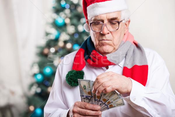 Senior man holding money on Christmas background Stock photo © photobac