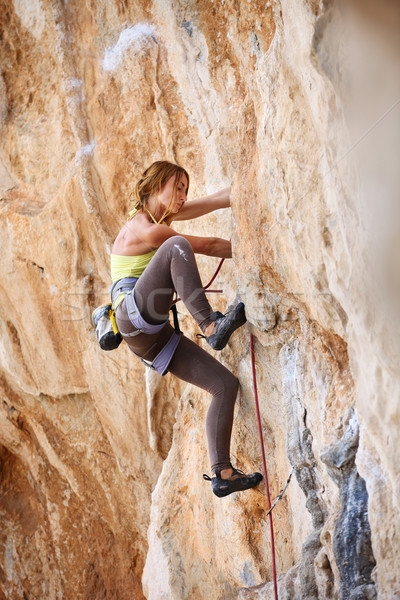 Young female rock climber a face of a cliff Stock photo © photobac