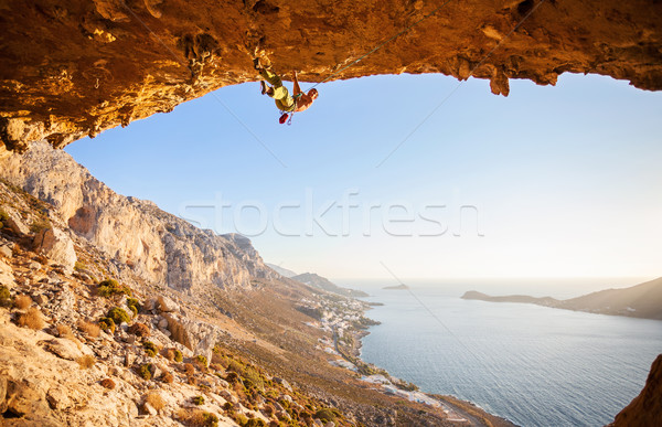 Male rock climber climbing along a roof in a cave Stock photo © photobac