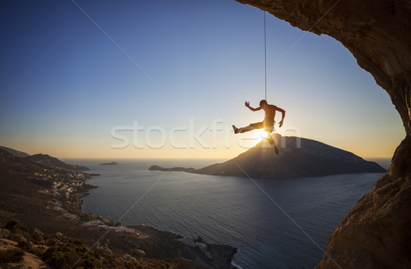 Male rock climber falling of a cliff at sunset Stock photo © photobac