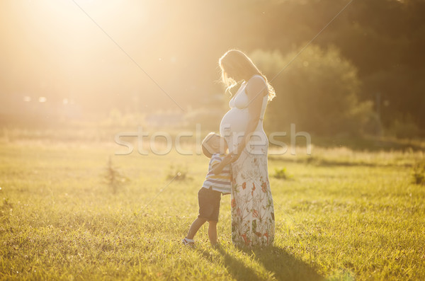 Pequeno menino beijando barriga grávida mãe Foto stock © photobac