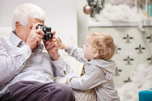 Senior man taking photo of his toddler grandson Stock photo © photobac