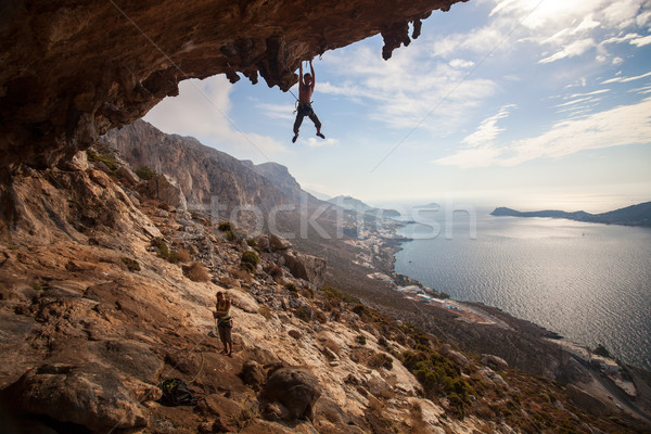 Rock climber climbing at the rock at sunset Stock photo © photobac
