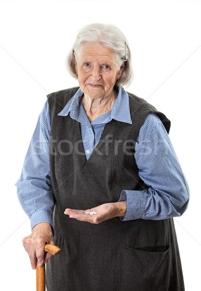 Senior woman holding medications over white Stock photo © photobac