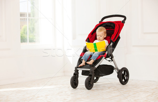 Little boy sitting in stroller and looking at book Stock photo © photobac