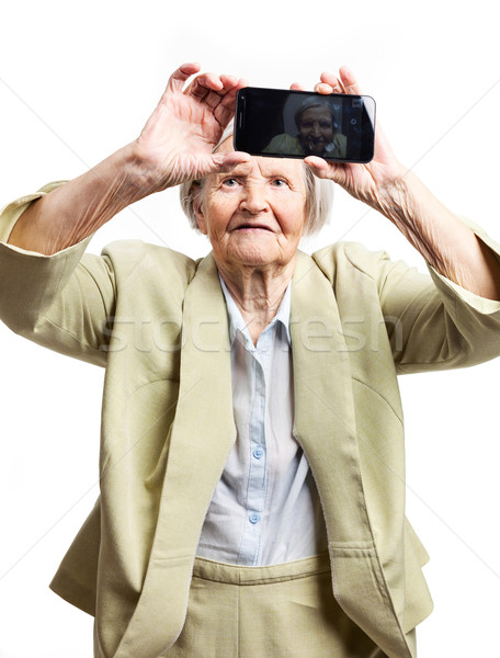 Elderly woman using mobile for taking selfie Stock photo © photobac