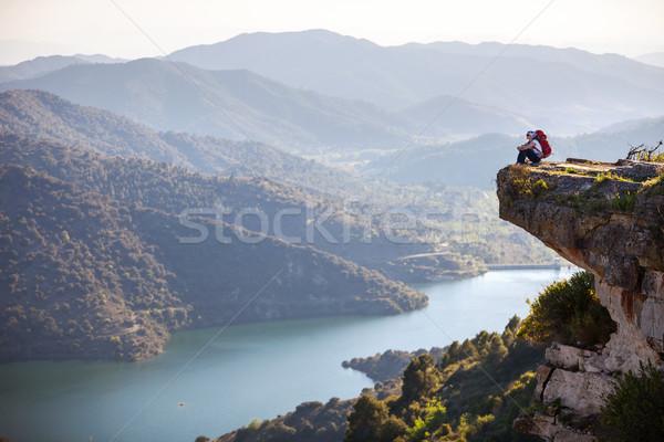 Female hiker sitting on cliff and enjoying view Stock photo © photobac