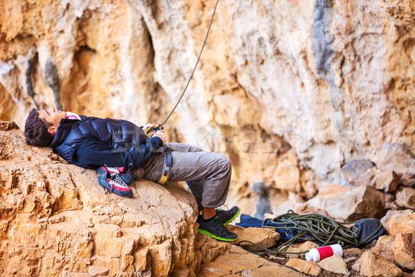 Man watching leading rock climber while belaying Stock photo © photobac
