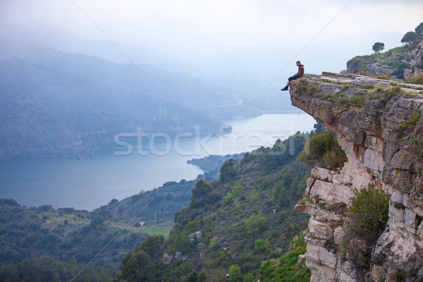 Young man sitting on edge of cliff Stock photo © photobac