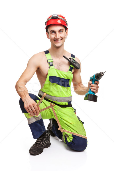 Stock photo: Contractor holding ruler and electric screwdriver