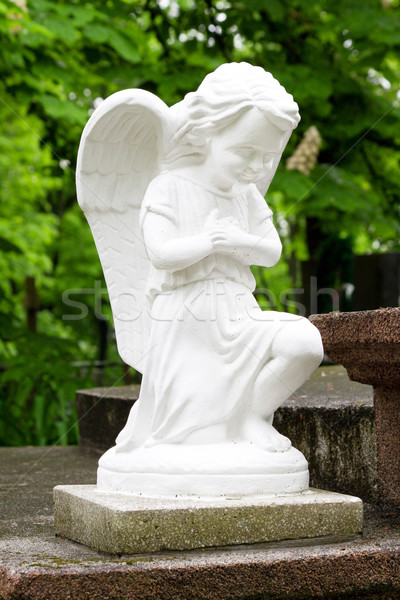 Stock photo: statue of an angel in prayer on the marble slabs in the garden