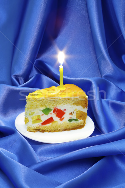 piece of fruit jelly cake with a lighted candle on a background of blue silk Stock photo © Photocrea