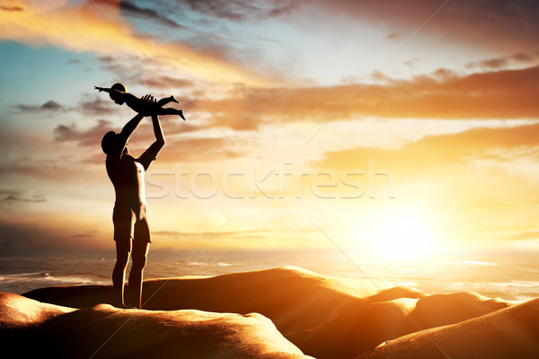 Stock photo: Happy father celebrating his little child by the seaside at sunset, summer time