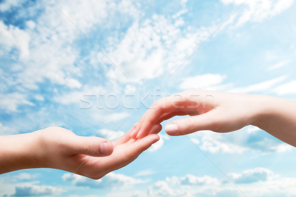 Man and woman hands touch in gentle, soft way on blue sunny sky Stock photo © photocreo