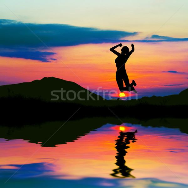 Silhouette of happy woman jumping at sunset Stock photo © photocreo