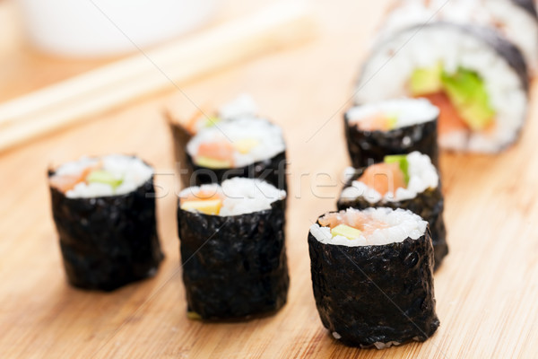 Sushi rolls with salmon, avocado, rice in seaweed and chopsticks Stock photo © photocreo