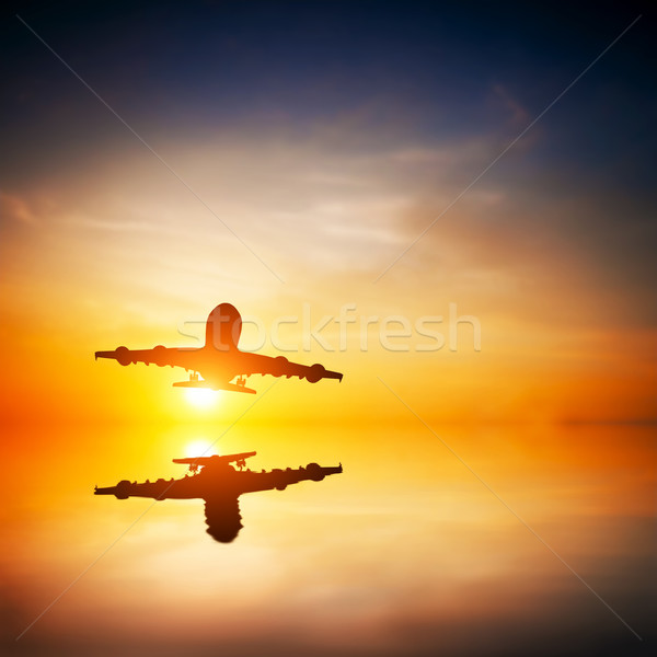 Airplane taking off at sunset. Silhouette of a flying passenger  Stock photo © photocreo