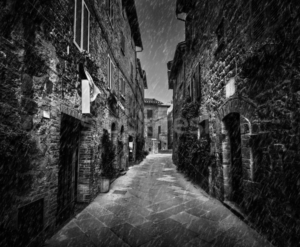 Dark street in an old Italian town in Tuscany, Italy. Raining, black and white Stock photo © photocreo