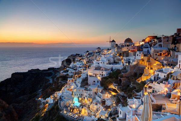 Oia town on Santorini island, Greece at sunset. Famous windmills Stock photo © photocreo