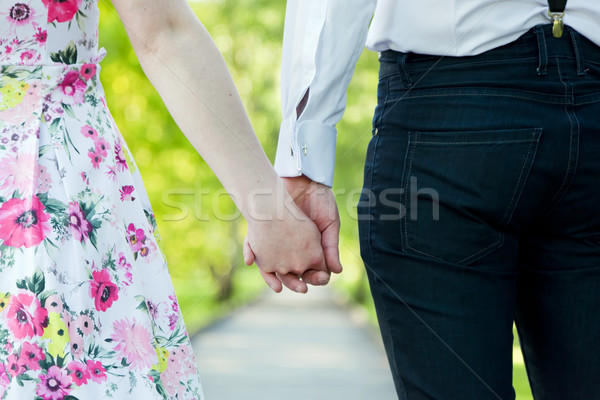 Stock photo: Young couple in love holding hands in summer park. Dating