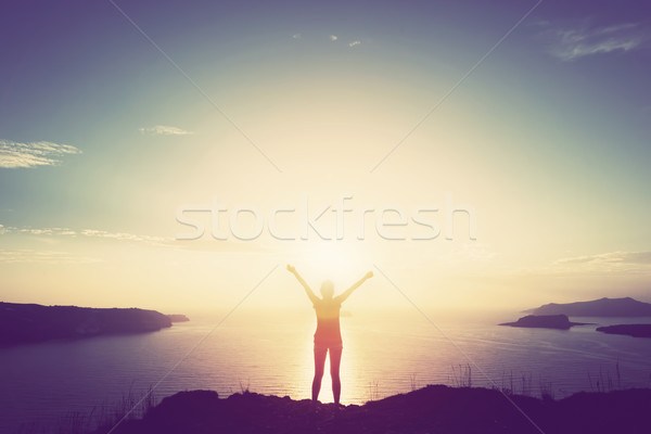 Happy woman with hands up on cliff over sea and islands at sunset Stock photo © photocreo