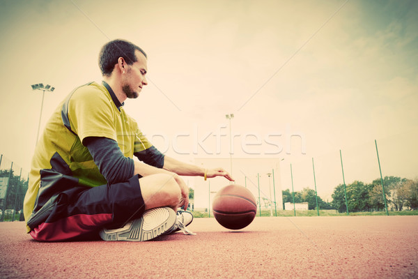 Young man on basketball court. Sitting and dribbling with ball Stock photo © photocreo