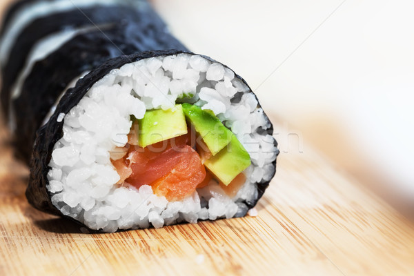 Sushi with salmon, avocado, rice in seaweed and chopsticks on wooden table Stock photo © photocreo