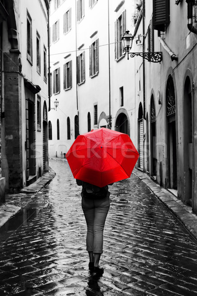 Woman with red umbrella on retro street in the old town. Wind and rain Stock photo © photocreo