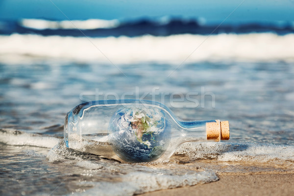 Earth in the bottle coming with wave from ocean. Environment, clean world message Stock photo © photocreo