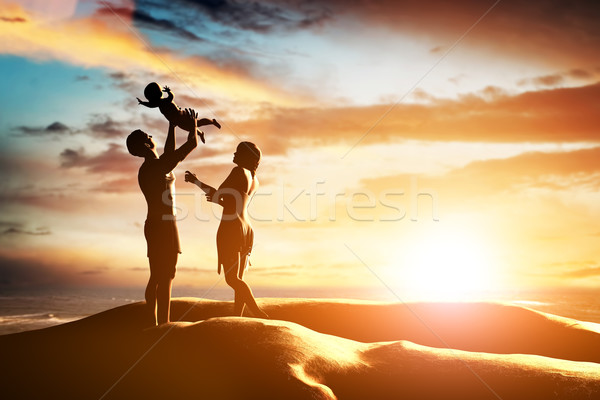 Stock photo: Happy family together, parents celebrating their little child by the seaside at sunset,