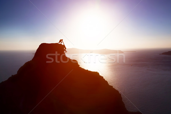 Climber giving hand and helping his friend to reach the top of the mountain. Help, support Stock photo © photocreo