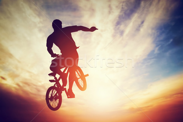 Man jumping on bmx bike performing a trick against sunset sky Stock photo © photocreo
