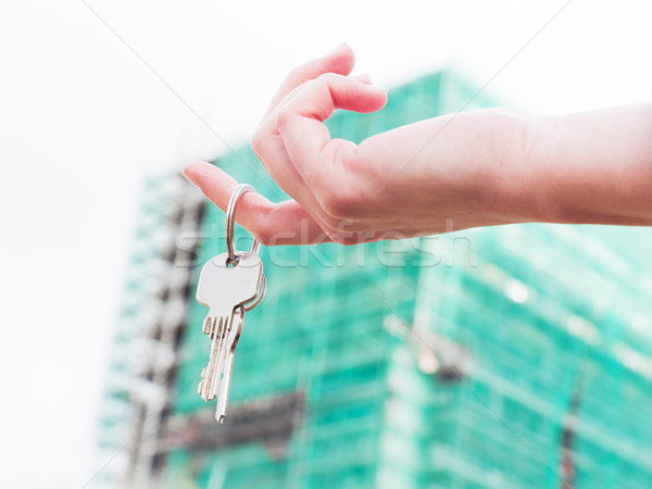 A real estate agent holding keys to a new apartment in her hands. Stock photo © photocreo