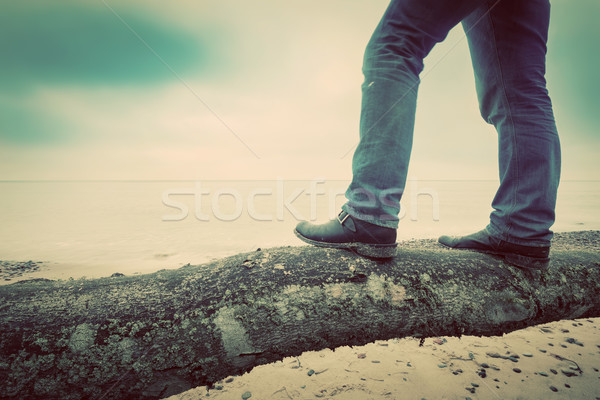 Man in jeans and elegant shoes standing on fallen tree on wild beach looking at sea. Vintage Stock photo © photocreo