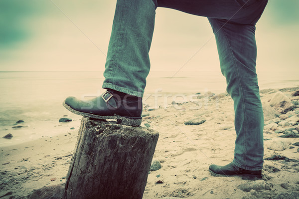 Man in jeans and elegant shoes leaning against trunk tree on wild beach looking at sea. Vintage Stock photo © photocreo