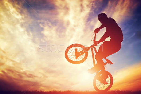 Man riding a bmx bike performing a trick against sunset sky Stock photo © photocreo