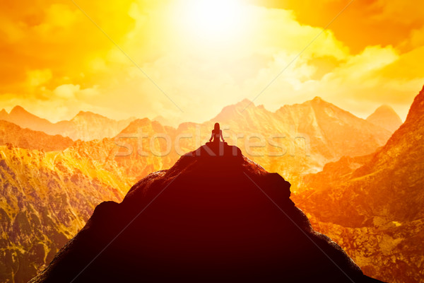 Woman meditating in sitting yoga position on the top of a mountains above clouds at sunset. Stock photo © photocreo