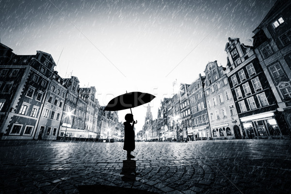 Child with umbrella standing alone on cobblestone old town in rain Stock photo © photocreo
