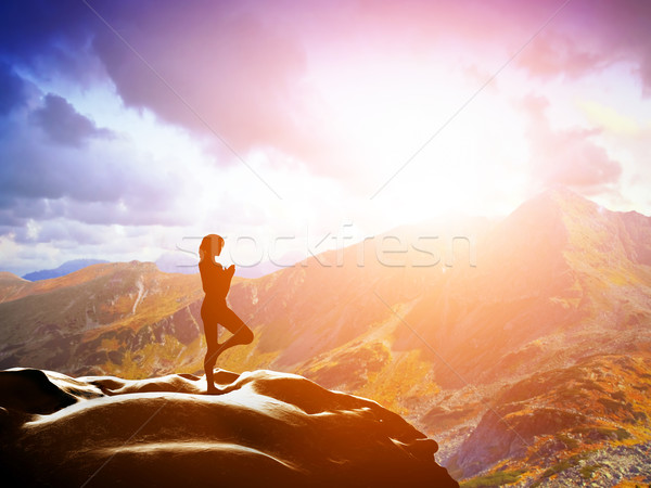 Woman standing in tree yoga position, meditating in mountains at sunset Stock photo © photocreo
