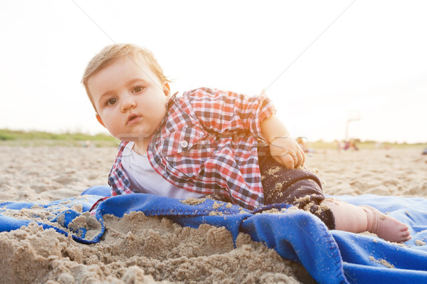 Handsome curious child lying on sand on the beach playing Stock photo © photocreo
