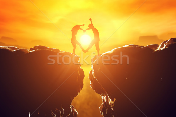 Happy couple in love making heart shape over precipice at sunset. Stock photo © photocreo