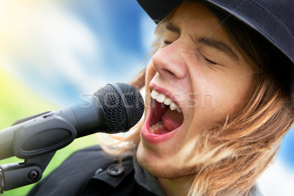 Young man sings to microphone Stock photo © photocreo