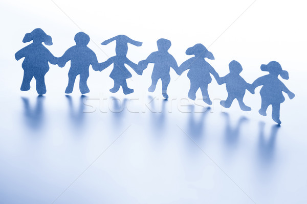 Paper children standing together hand in hand.  Stock photo © photocreo