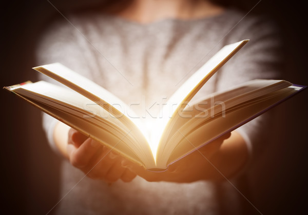 Light coming from book in woman's hands in gesture of giving Stock photo © photocreo