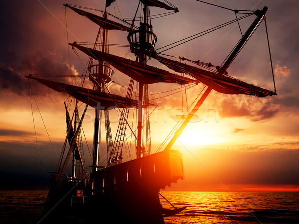 Old ancient pirate ship on peaceful ocean at sunset.  Stock photo © photocreo