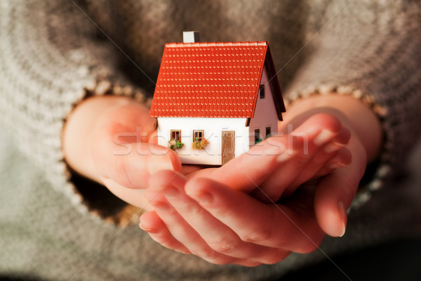 Woman holding a small new house in her hands. Real estate, mortgage Stock photo © photocreo
