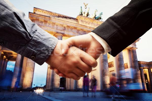 Business in Berlin. Handshake on Brandenburg Gate background. Stock photo © photocreo