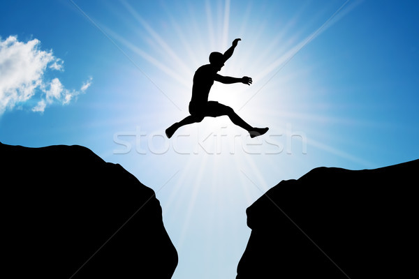 Stock photo: Man jumping over precipice between two rocky mountains