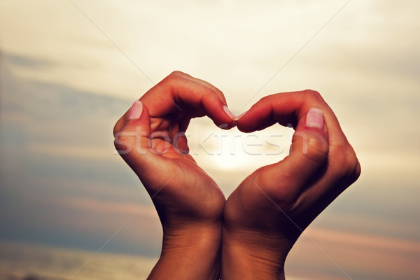 Heart shape in woman's hands at sunse Stock photo © photocreo