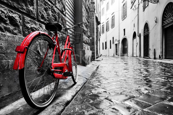 Retro vintage red bike on cobblestone street in the old town. Color in black and white Stock photo © photocreo